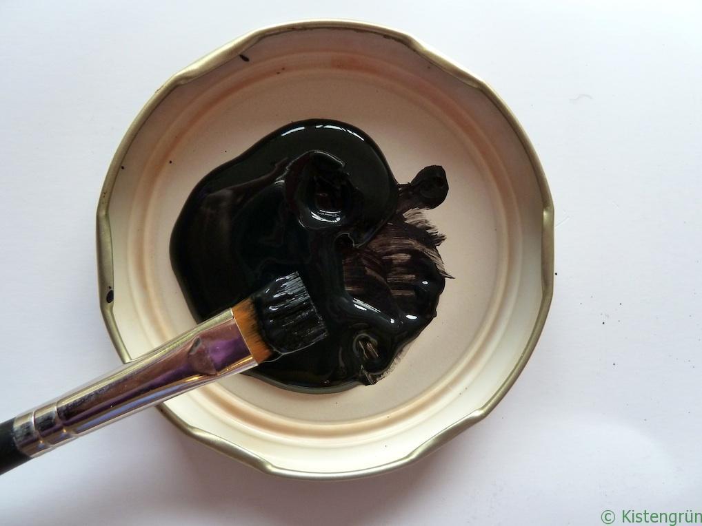 Ein Pinsel liegt auf dem Deckel eines Schraubglases, der mit schwarzem Tafellack gefüllt ist.