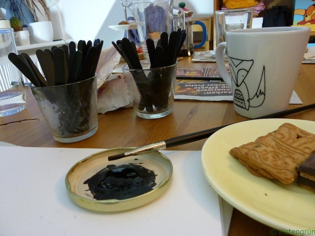 Pflanzenschilder basteln: Auf einem Tisch stehen Gläser mit bereits bemalten Steckern.