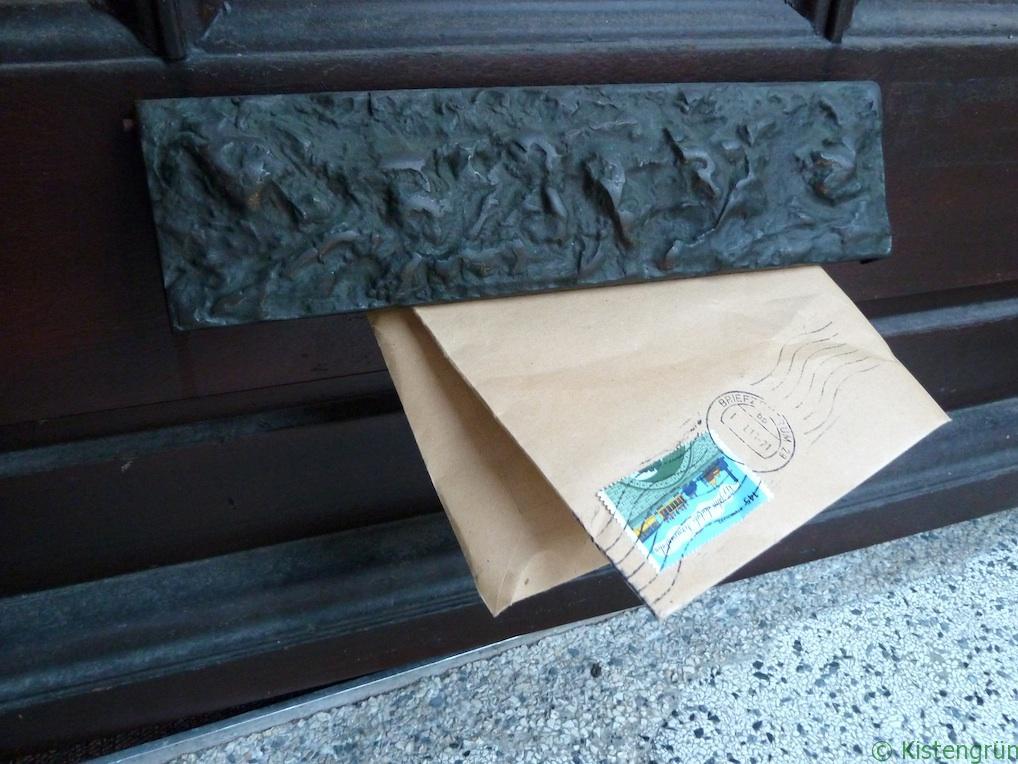 großer Briefumschlag in einem Briefkastenschlitz